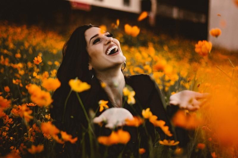 woman-laughing-in-orange-flowers_800